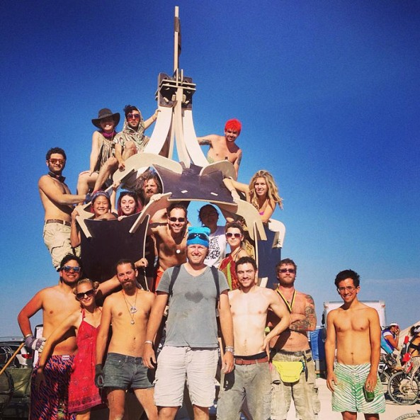 Billionaire Burner Moskovitz at Burning Man 2013. He is to the left, clinging on to the structure with his shirt off